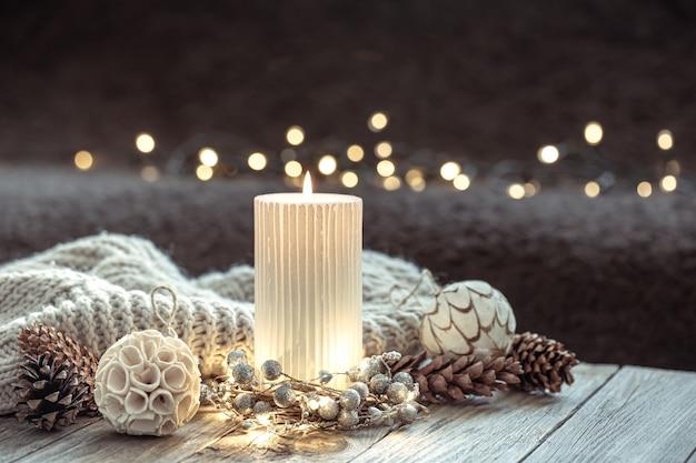 Fundo festivo de inverno com vela acesa e detalhes de decoração para casa no fundo desfocado com bokeh.