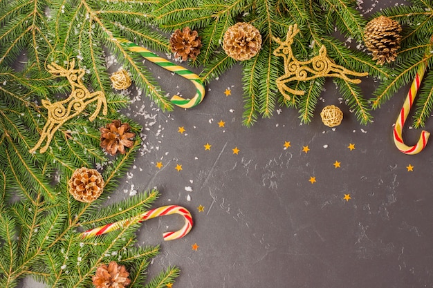 Fundo festivo de natal com ramos de abeto, veado dourado e cones, decoração tradicional - caramelo - cana, confetes das estrelas.