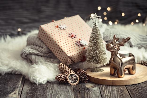Fundo festivo de natal com veado de brinquedo com uma caixa de presente, fundo desfocado com luzes douradas, fundo festivo na mesa de deck de madeira e suéter aconchegante no fundo