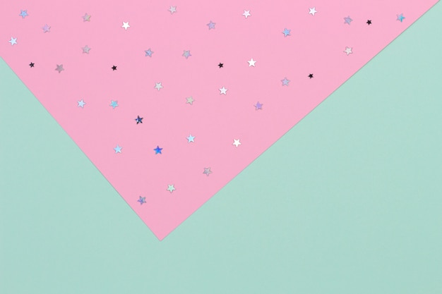 Fundo festivo geométrico abstrato. verde claro e rosa pastel com fundo de papel de estrelas de brilho. vista do topo
