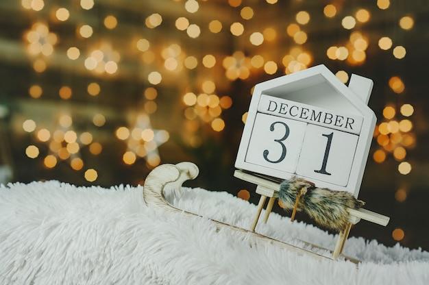 Fundo festivo na véspera do ano novo, com um calendário de contagem regressiva em 31 de dezembro no fundo dos gerlyands luminosos com estrelas.