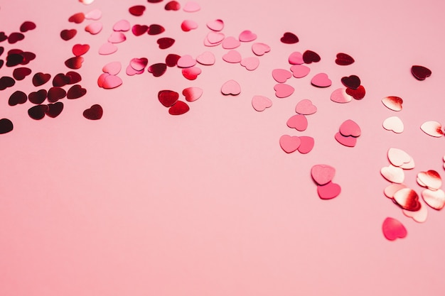 Fundo festivo vermelho e rosa com confetes em forma de coração vermelho.
