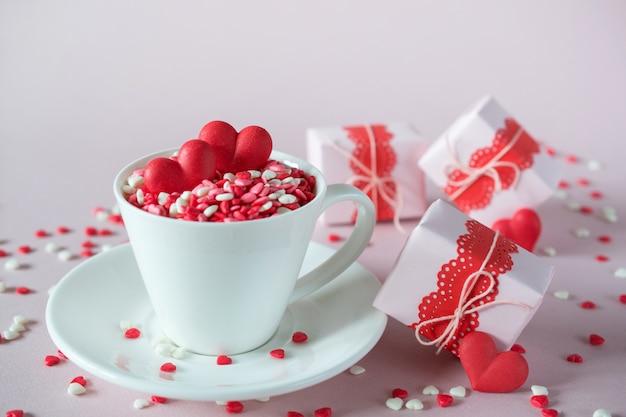 Fundo festivo. xícara de café, cheia de doces multicoloridos polvilha corações de doces de açúcar e embalagem de presentes de dia dos namorados. conceito de amor e dia dos namorados.