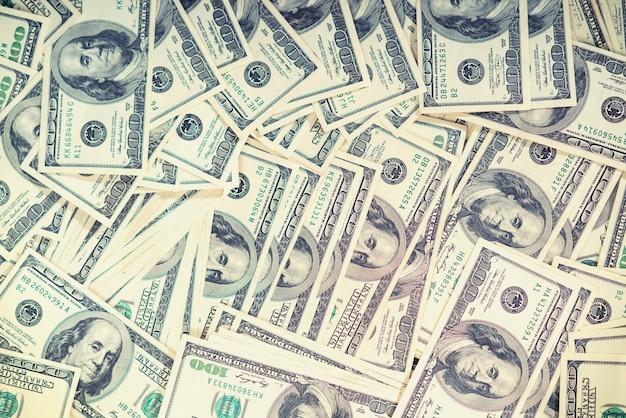 Fundo financeiro com camadas de notas de 100 dólares americanos dispostas sobre uma mesa em uma visão aérea de quadro inteiro