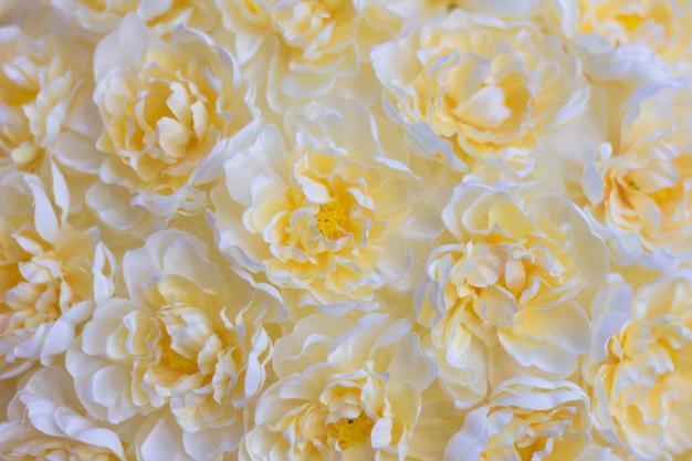 Fundo floral amarelo. muitas flores artificiais na composição colorida.