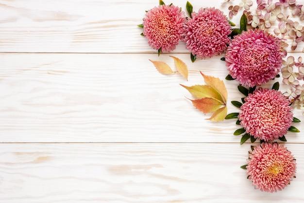 Fundo floral do outono - ásteres cor-de-rosa na tabela de madeira branca.
