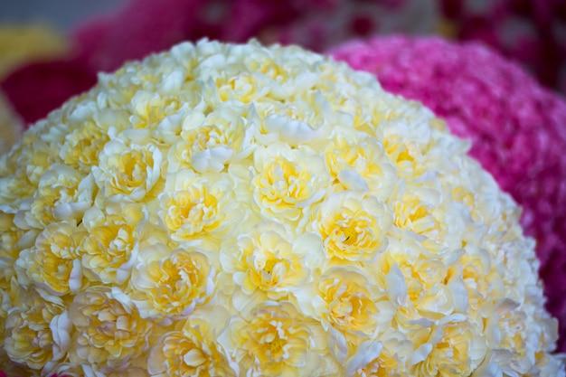 Fundo floral monte de flores rosa amarelas artificiais na composição colorida