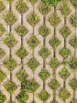 Fundo geométrico de tijolos com piso ecológico e grama verde