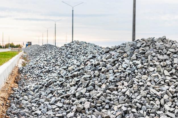 Fundo industrial com pilha de cascalho. extração de cascalho. construção de estradas. pilhas de cascalho no canteiro de obras.