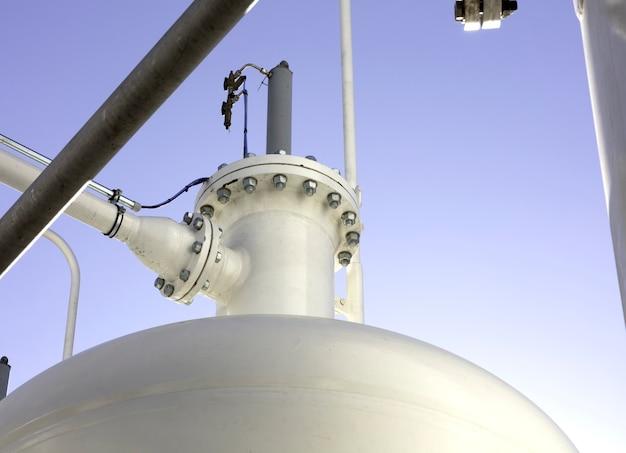 Fundo industrial com tubos, juntas, parafusos e tanque de pressão de cor branca com céu azul como fundo