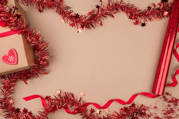 Fundo isolado um presente em papel ofício, com uma fita vermelha em que jazem meias de doces, luvas e um coração de papel, é cercado por enfeites de natal vermelhos, rolos com embalagens.