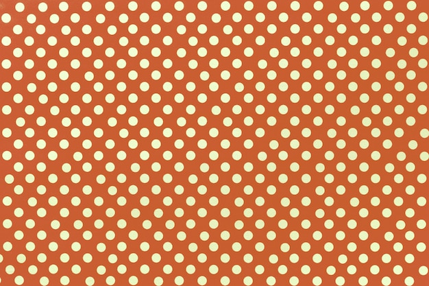 Fundo laranja claro do papel de embrulho com um de bolinhas douradas