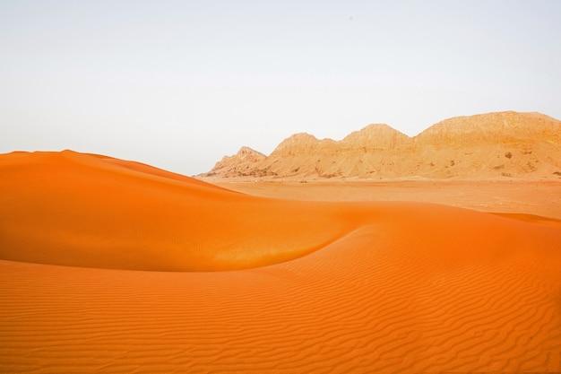 Fundo laranja do deserto de dubai com montanha e areia