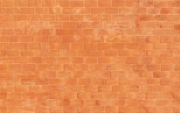 Fundo laranja velho da parede de tijolos