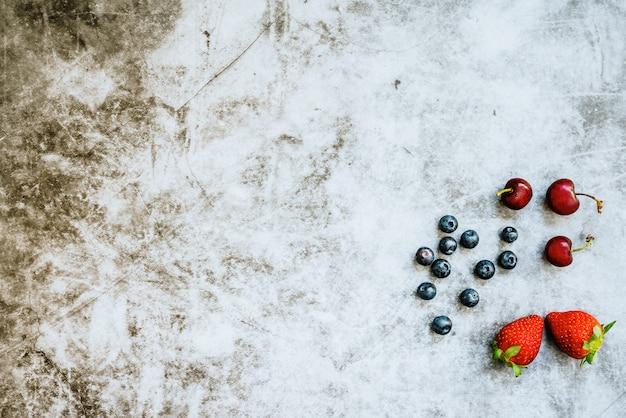 Fundo limpo para alimentos saudáveis com frutas vermelhas de um lado
