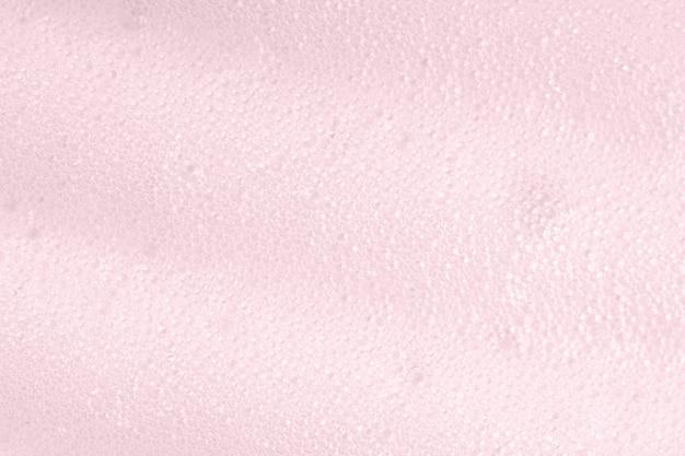 Fundo macro de espuma rosa com bolhas. closeup de superfície com sabão. produto de limpeza com espuma para a pele