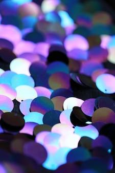 Fundo macro de lantejoulas. lantejoulas holográficas em tom roxo e azul