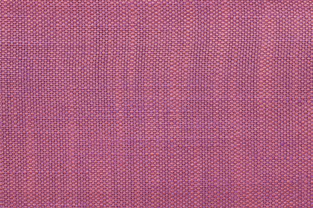 Fundo magenta de matéria têxtil com teste padrão quadriculado, close up. estrutura da macro de malha.