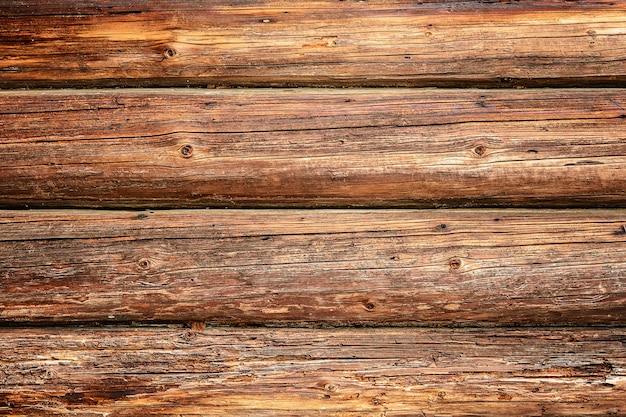 Fundo magnífico de uma parede velha texturizada feita de vigas de madeira marrons.