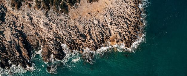Fundo marinho dramático costa rochosa do mar adriático, ondas espumosas brancas batem contra a pedra