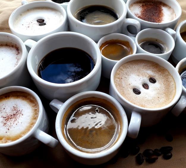 Fundo marrom com várias xícaras de diferentes tipos de cafés