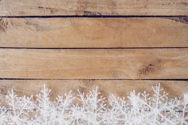 Fundo marrom de madeira do natal com flocos de neve e decoração do natal.