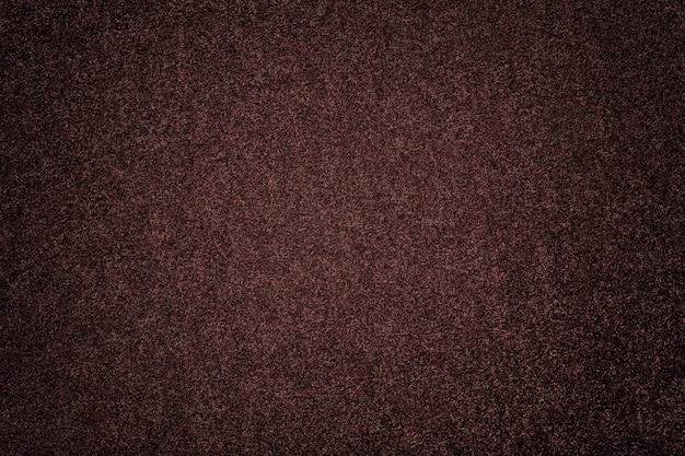 Fundo marrom escuro fosco de tecido de camurça. textura aveludada de feltro de lã umber com vinheta.