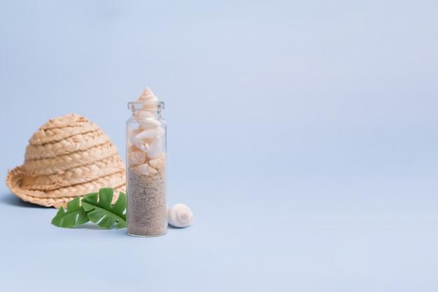 Fundo minimalista de verão com mini garrafa, pequenas conchas, areia