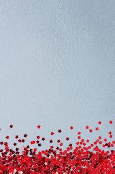 Fundo mínimo de natal com confete vermelho em cinza