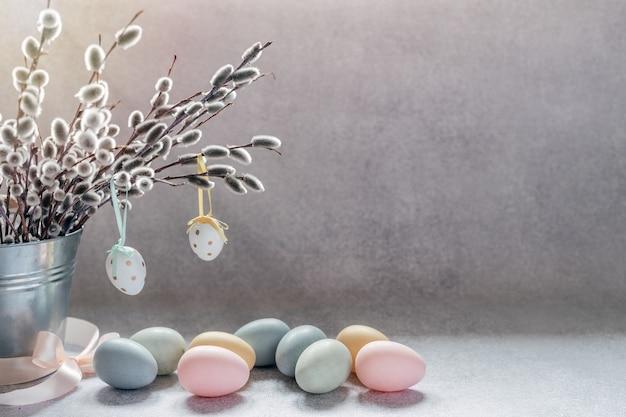 Fundo mínimo de páscoa com ramos de amentilho de salgueiro em um balde decorativo e ovos de páscoa coloridos com espaço de cópia