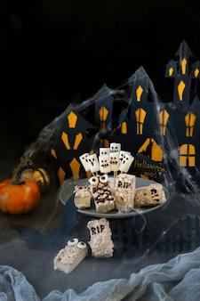 Fundo moderno de halloween. barra de chocolate de halloween: monstros engraçados feitos de biscoitos com chocolate e close-up de marshmelow fantasmas em cima da mesa