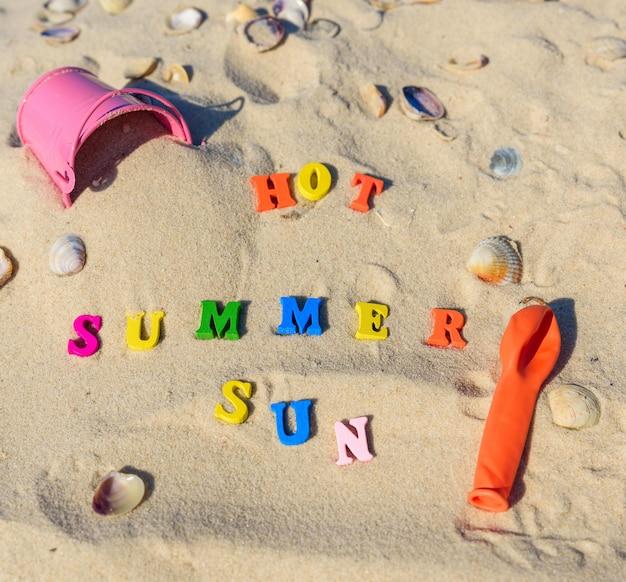 Fundo na areia com inscrições de verão, sol, quente
