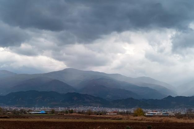 Fundo natural bonito com pequena cidade sob a paisagem e nuvens sobre as montanhas enevoadas. foco seletivo