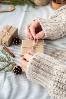 Fundo natural de natal, caixas de presente de artesanato, cones, árvore de natal em cima da mesa, close-up, estilo retro. uma garota com um suéter está embalando presentes. a atmosfera feliz do feriado.