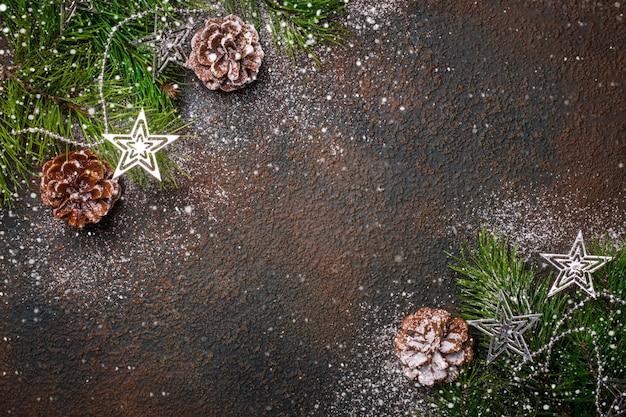 Fundo natural de natal com galhos de pinheiro, cones e neve.