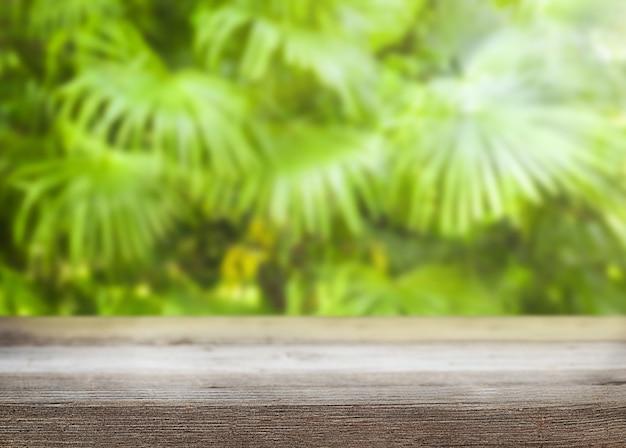 Fundo natural de verão com base de madeira e vista nas folhas de palmeira desfocadas