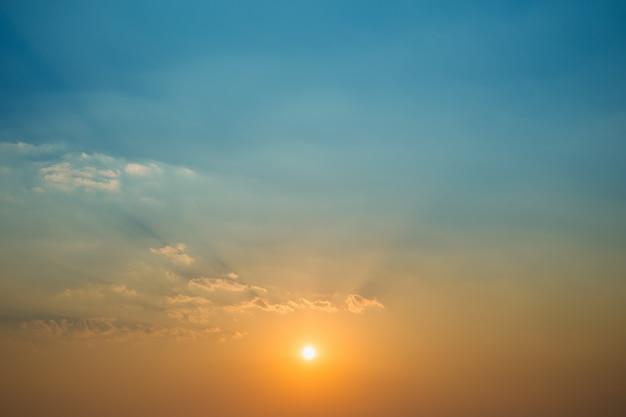 Fundo natural do céu azul e alaranjado crepuscular com a nuvem na noite após o por do sol.
