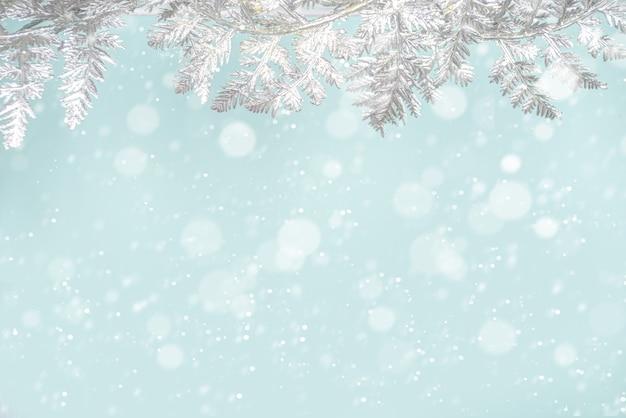 Fundo nevado festivo de inverno e natal com ramos de decoração de natal prateados,