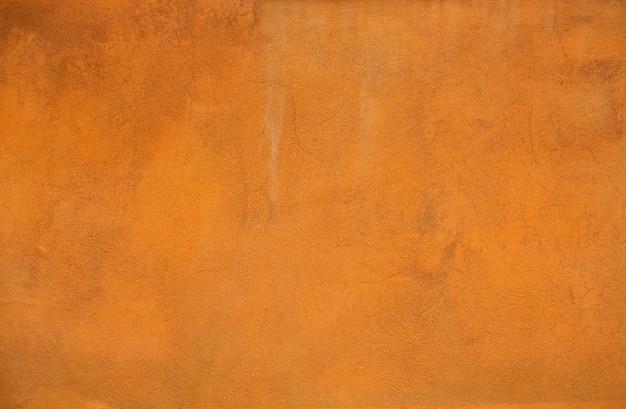 Fundo ou textura alaranjada do estuque da cor. luz brilhante parede rebocada de um edifício