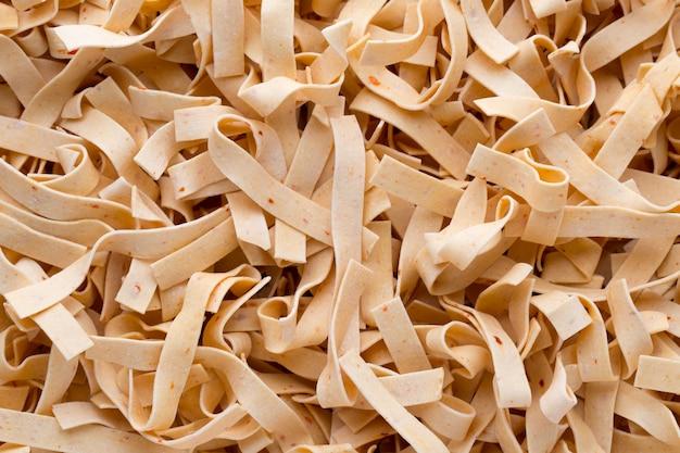 Fundo ou textura de alimentos crus de massa de macarrão italiano close-up.