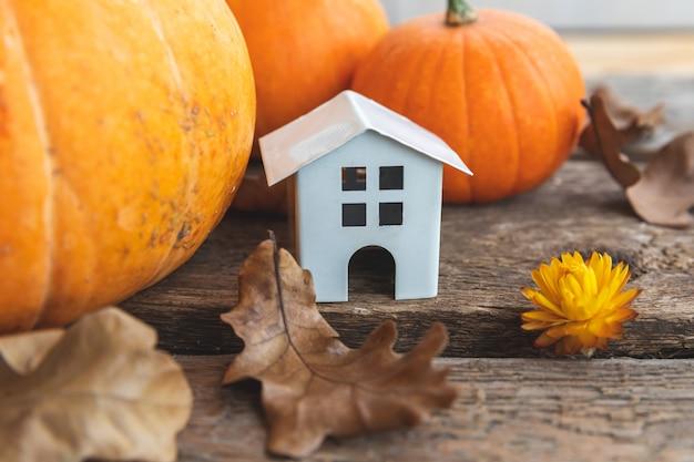 Fundo outonal. casa de brinquedo e abóbora em fundo de madeira. espaço da cópia do banner de ação de graças. humor hygge, conceito de mudança de estações. olá outono com festa de halloween em família.