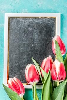 Fundo para parabéns, cartões de felicitações. flores de tulipas primavera fresca com lousa