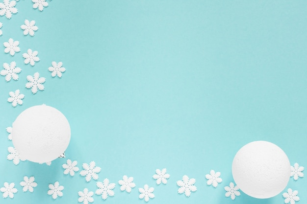 Fundo pastel de férias, flocos de neve brancos e bola de natal em um fundo azul suave, vista de cima plana