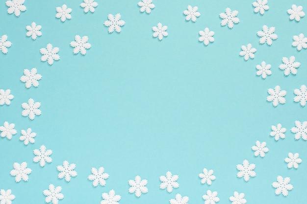 Fundo pastel de férias, flocos de neve brancos sobre um fundo azul suave, vista de cima plana