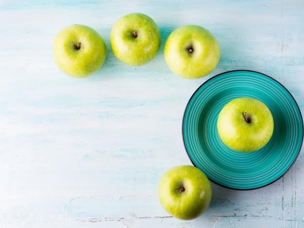 Fundo pastel verde com maçãs.