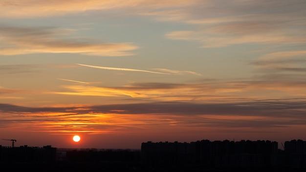 Fundo por do sol dramático bonito. céu laranja com sol, nuvens e silhuetas negras de prédios urbanos