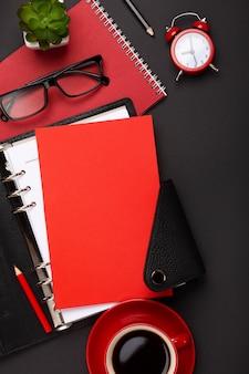 Fundo preto com copo de café vermelho, o bloco de notas, despertador e flores na vista superior