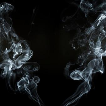 Fundo preto com duas silhuetas de fumaça em movimento