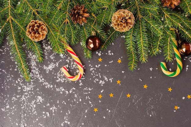 Fundo preto de ano novo coberto de neve com ramos de abeto, brinquedos, confetes. vista do topo. espaço para texto.