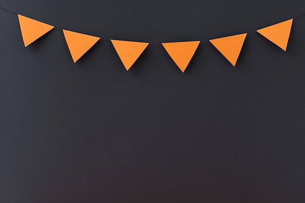 Fundo preto de férias com pequenas bandeiras laranja e local para texto